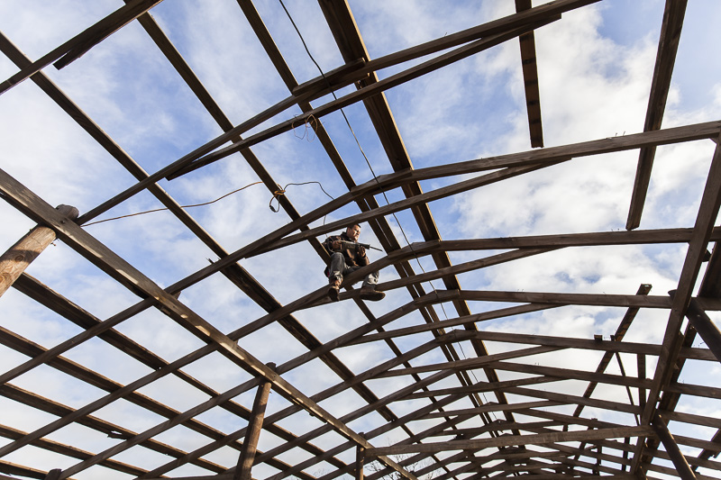 A worker dismantles an old barn to make way for a new one at Johnson's Backyard Garden, Austin, TX.