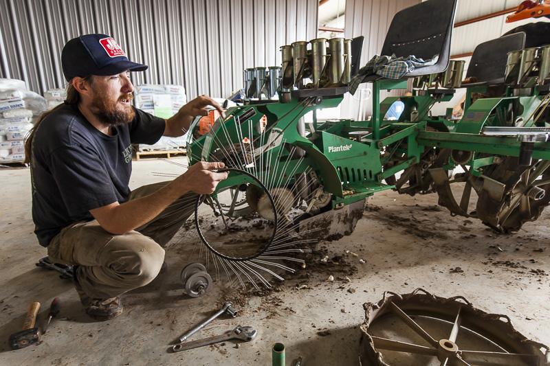 Montana does some maintenence work on the transplanter at Johnson's Backyard Garden, Austin, TX.