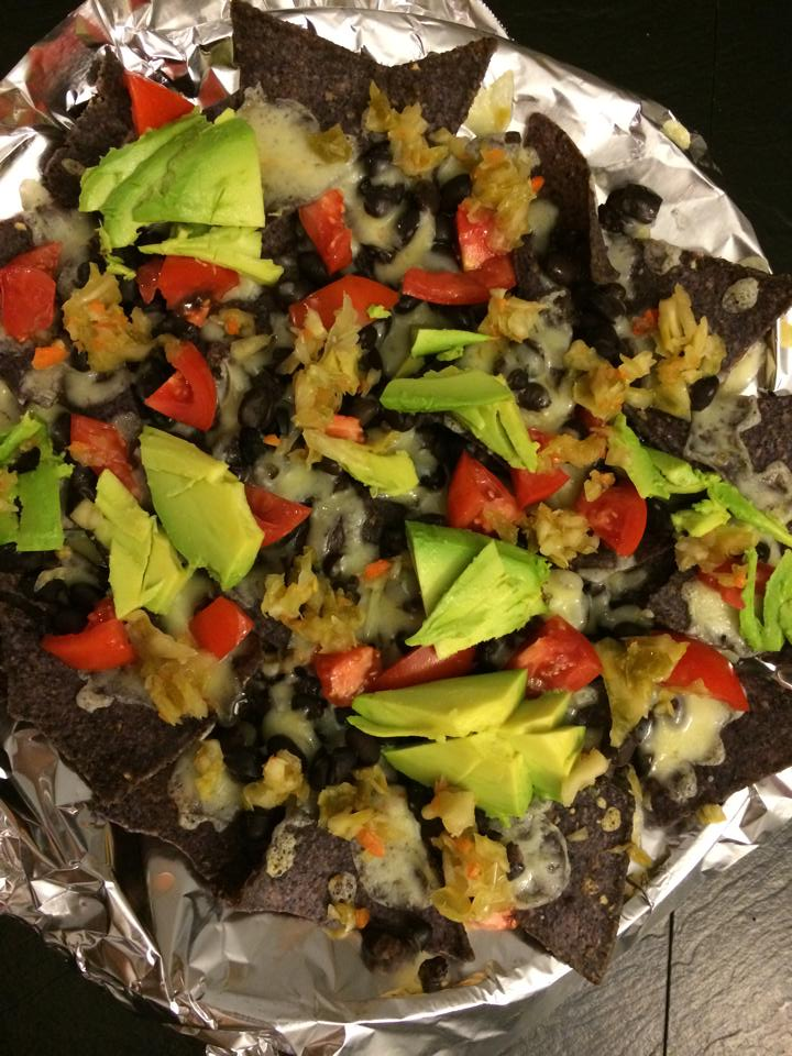 Nachos topped with heirloom tomatoes, black beans, cheddar cheese, avocado and Vibrant Veggies' Roasted Green Chile kraut. Never better!