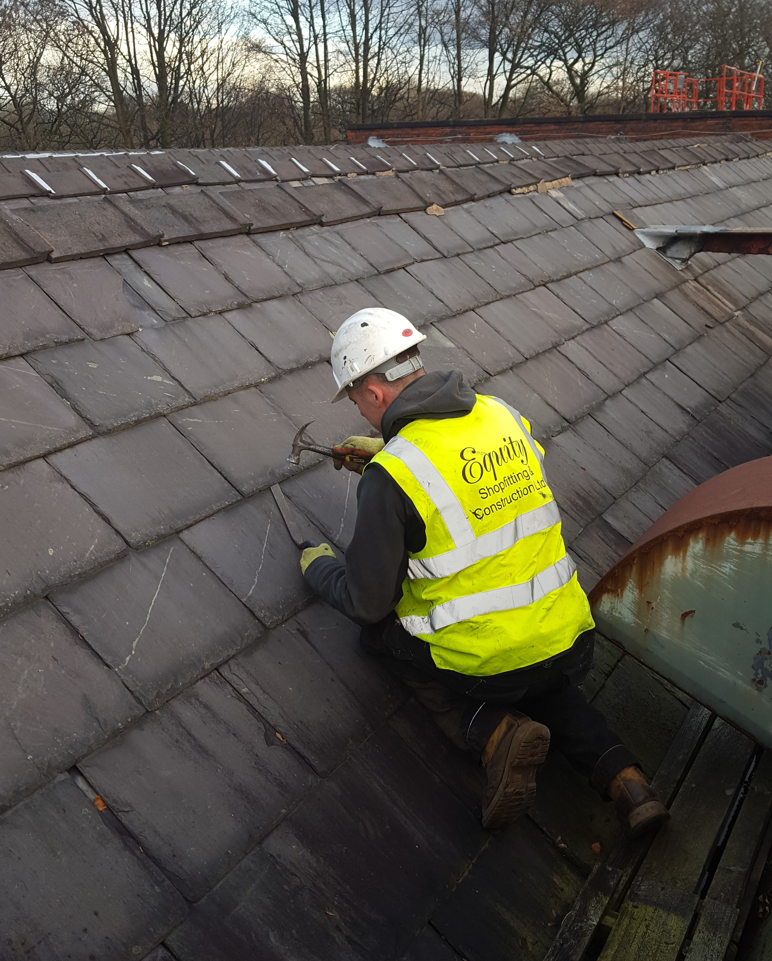 A roofer working on a slate roof.