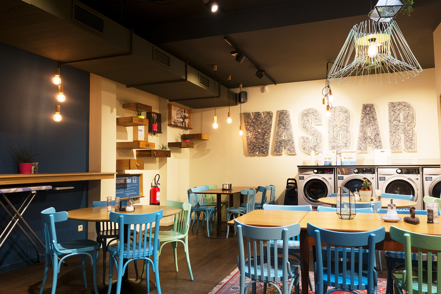 Inside WASBAR in Antwerp, with blue chairs and washing machines