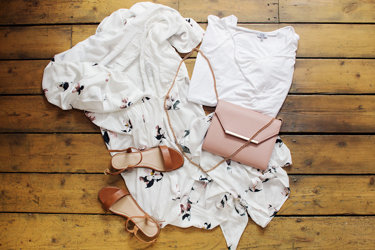 Fashion flatlay with summer dress, white t-shirt, sandals and pink bag on floorboards