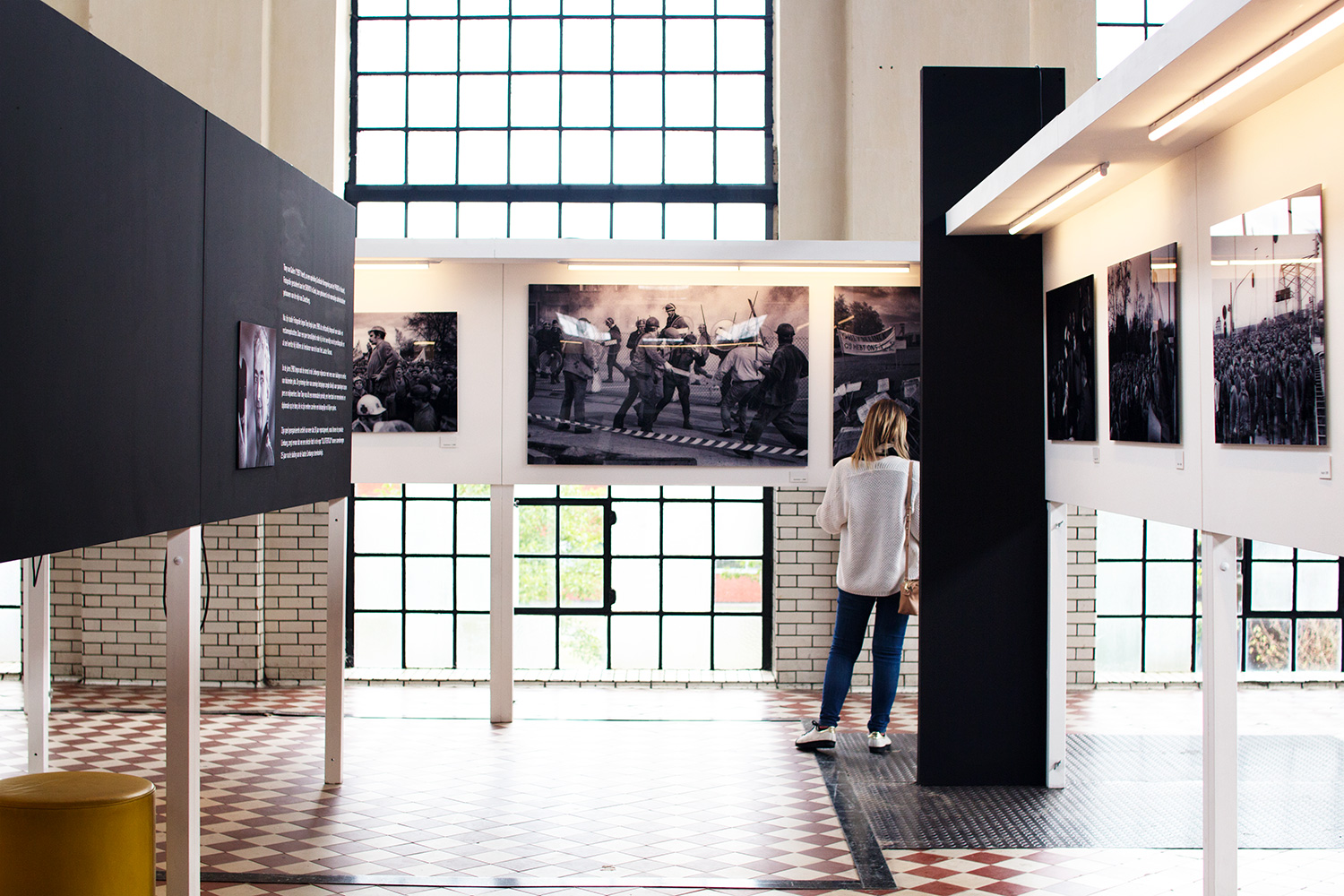 Person studying the exhibition pictures of coal miners protests at C-mine, Genk