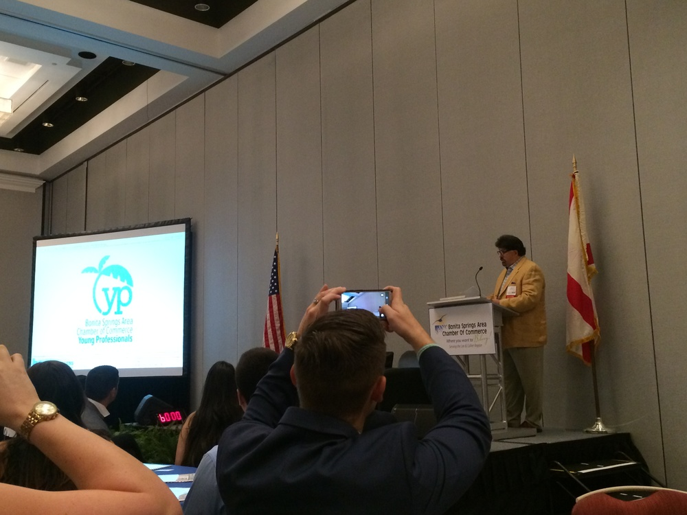 "Bryon McCartney, chief designer and idea guy at Be Brilliant Marketing, was on hand to unveil the new logo at the Bonita Springs Area Young Professionals' inaugural ""In Your Future"" Summit, in September 2015."