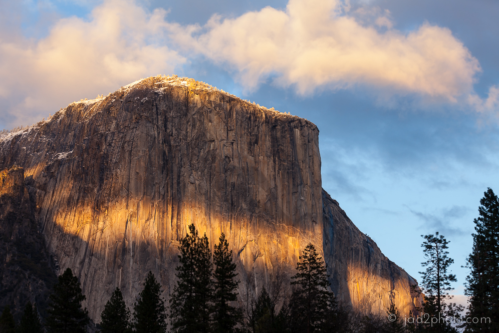 A band of setting sun paints El Cap's midsection following a fresh snowfall.