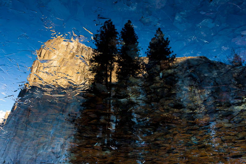 A sunrise on El Capitan is reflected off an icy Merced.