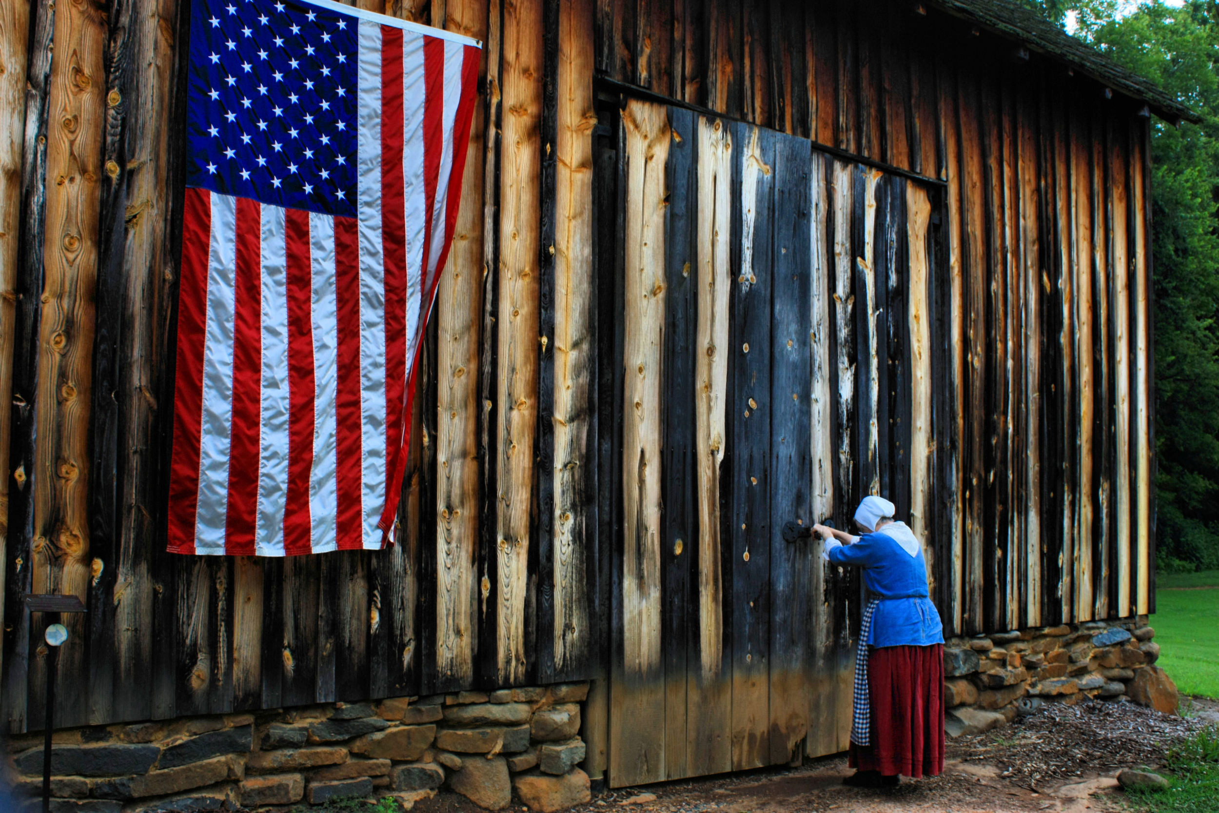 A woman dressed as a Moravian wandered into the shot as I was trying to picture this huge Moravian shed with an American Flag.  She made the shot more poignant.