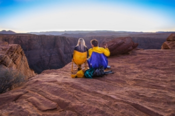 A couple sits on the edge of the lookout to enjoy the sunset at Horseshoe Bend with a bottle of wine and some cigars. Others bring a blanket to sit and enjoy the moment.