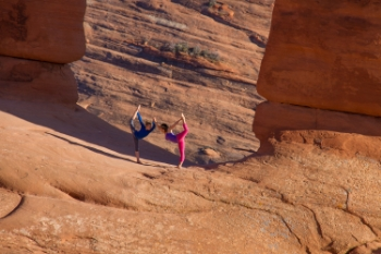 A mother-daughter duo strike a pose under the Delicate Arch in Utah's Arches National Park. People take pictures under the arch as the mile-and-a-half hike to the summit makes for a once in a lifetime experience.