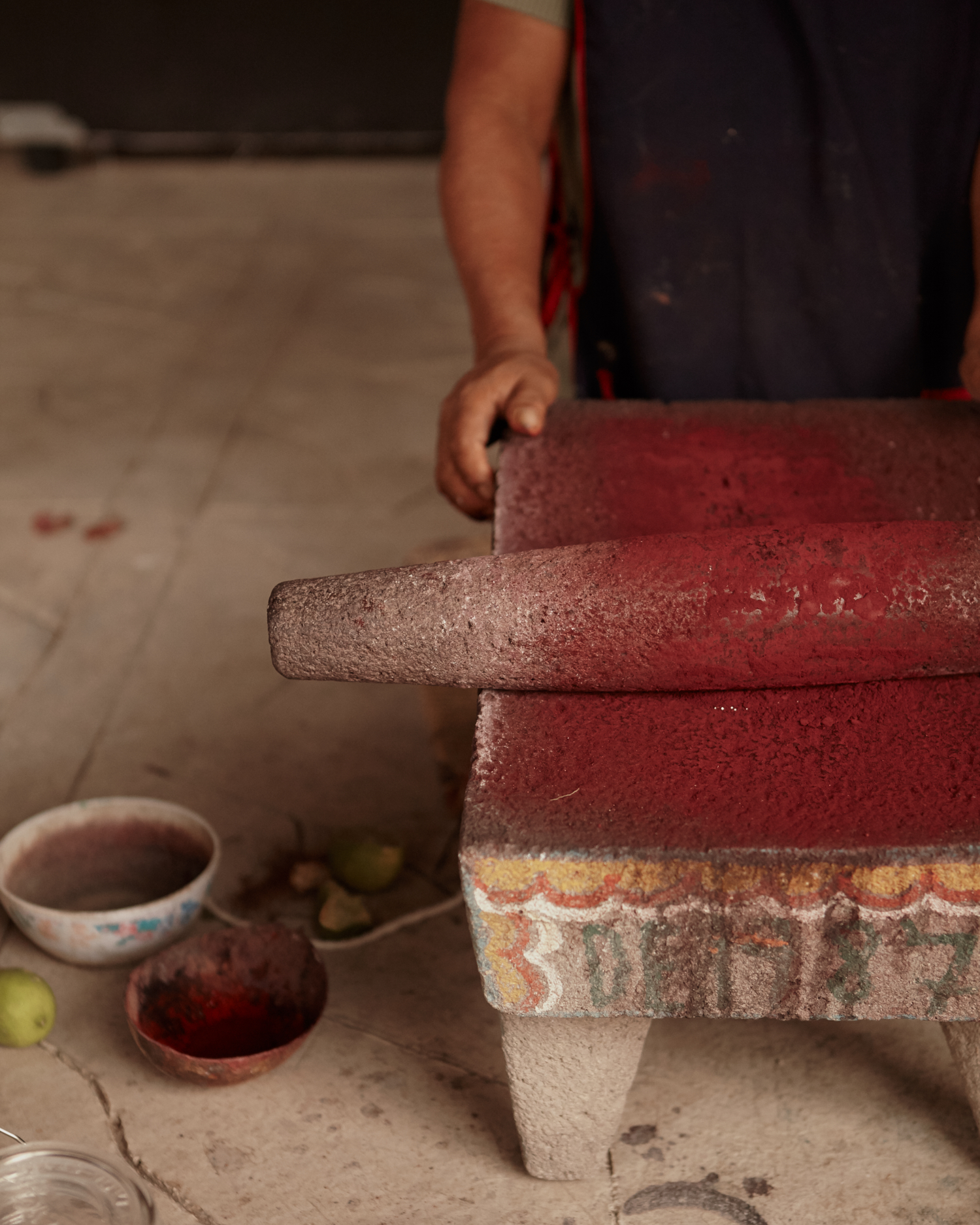 A metate, or mealing stone, is used to methodically grind the dried cochineal to reveal it's deep red treasure