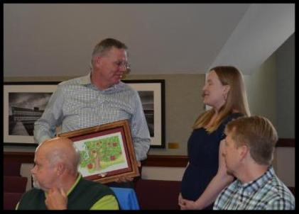 Outgoing board member Welcome Sauer was recognized with Year of the Apple artwork