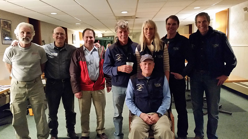 RACE TEAM AFTER SKI WAXING!     (They look exhausted—Ed.)   Left-to-right: Steve Zilli, Fast Fred Forbes, Rich Zober, Paul Fowser, Susan Maximuk, John Hadfield and Ron Konsza. Seated: Bill Champion