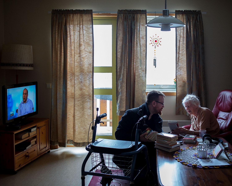 Deanu-Unjárgga girjebusse – Bokbussen Tana-Nesseby  Biblioteknr.: NO-2200091 Tana, Finnmark Fotografert: 2015  98 år gamle Edith Bønå er den eldste låneren på ruta til Jørgen Betten og bokbussen. Hun er svært tunghørt, men ser godt og er en storforbruker av serieromaner. For tiden er det  Malmbyen  av Aud Midtsund det går i. En fordel med pocketbøkene er at de ikke er så tunge å holde i for et par armer som har løftet nok for et helt liv.
