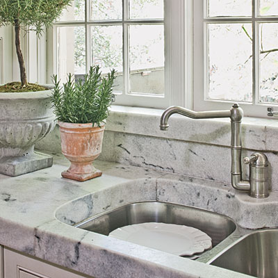Several tons of old marble blocks salvaged from a historic theater being torn down in Nashville is honed into 3-inch-thick countertops and a herringbone-patterned backsplash.