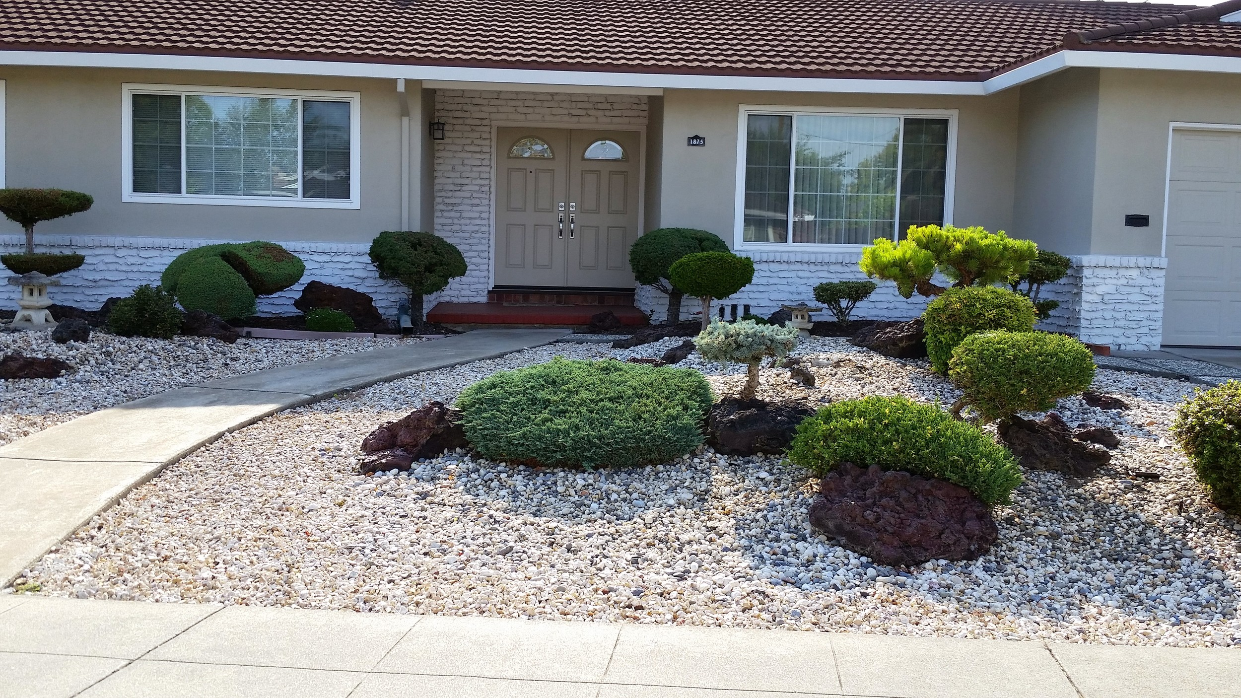 Vintage landscape with decorative rock and highly stylized shrubs.