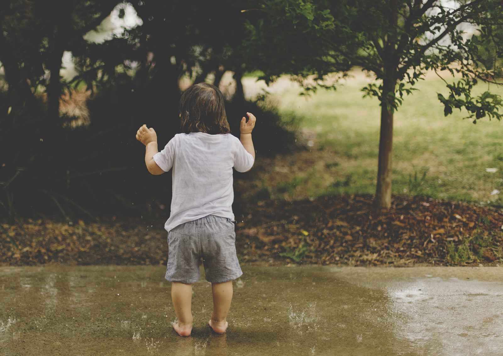 Toddler experiencing a rain shower!