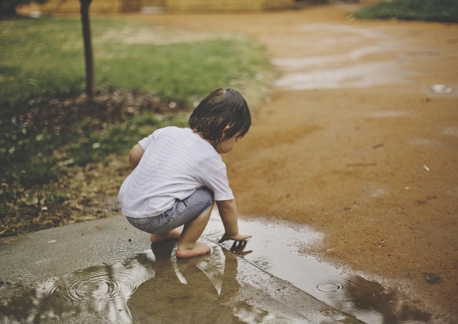 Toddler playing in the muddy puddle!