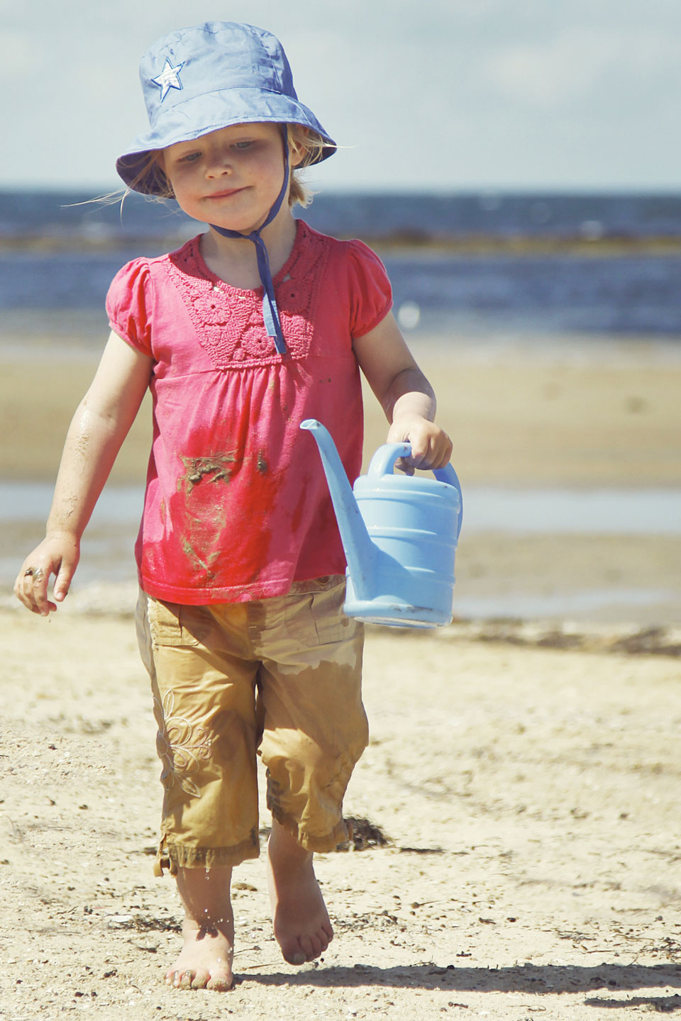Little toddler carrying bucket of water at the beach!