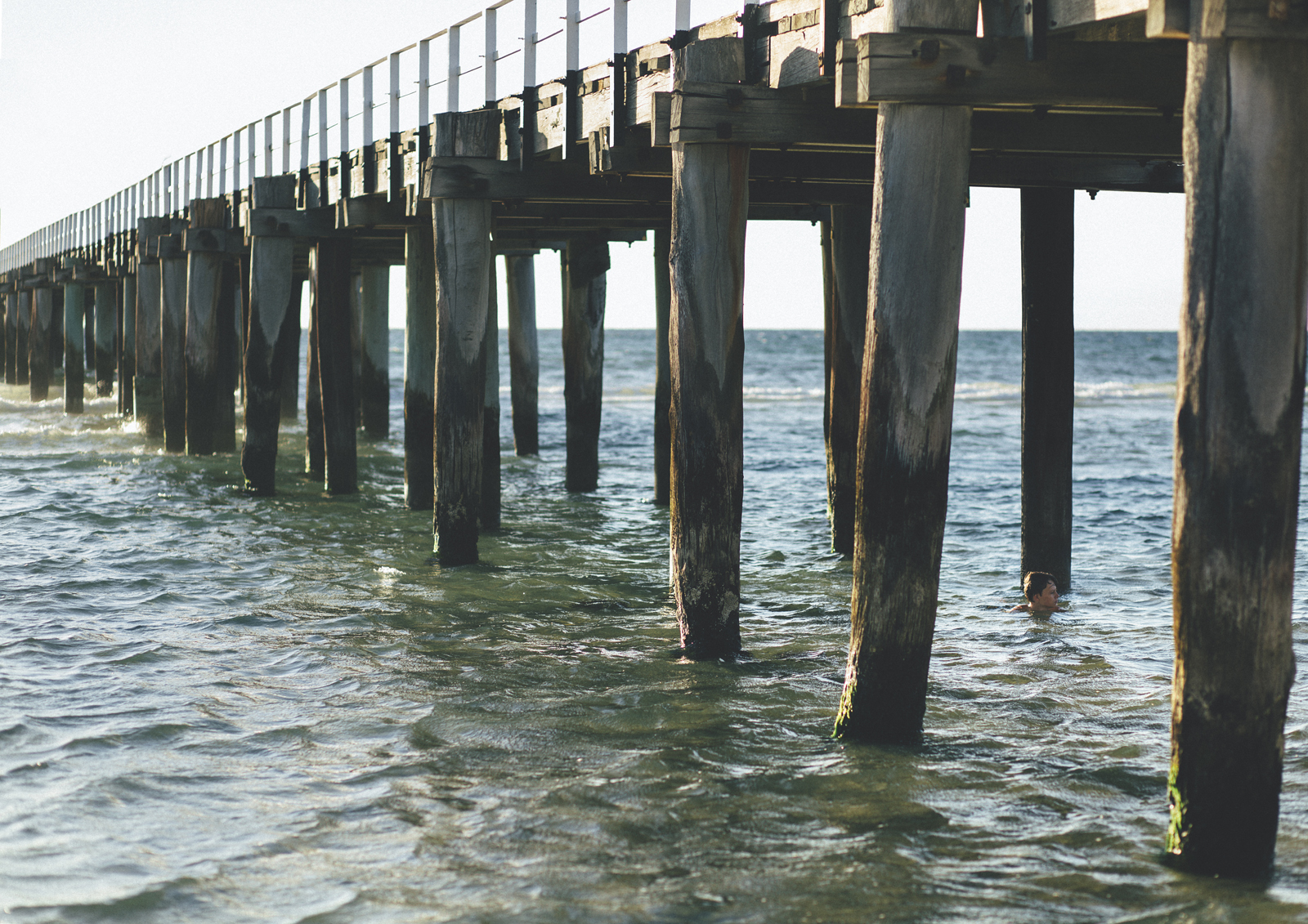 Child swimming under pier - Children's Photography Melbourne