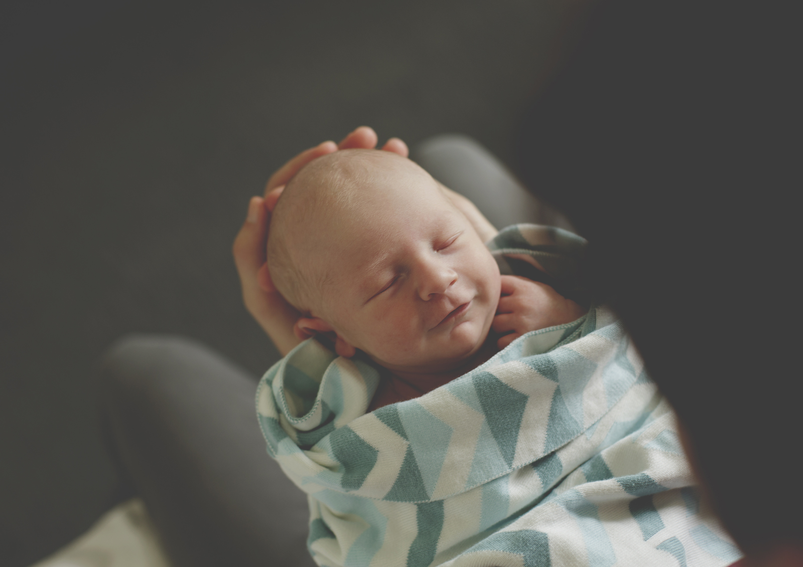 Daddy holding newborn son whose smiling - Natural Newborn Photography Melbourne