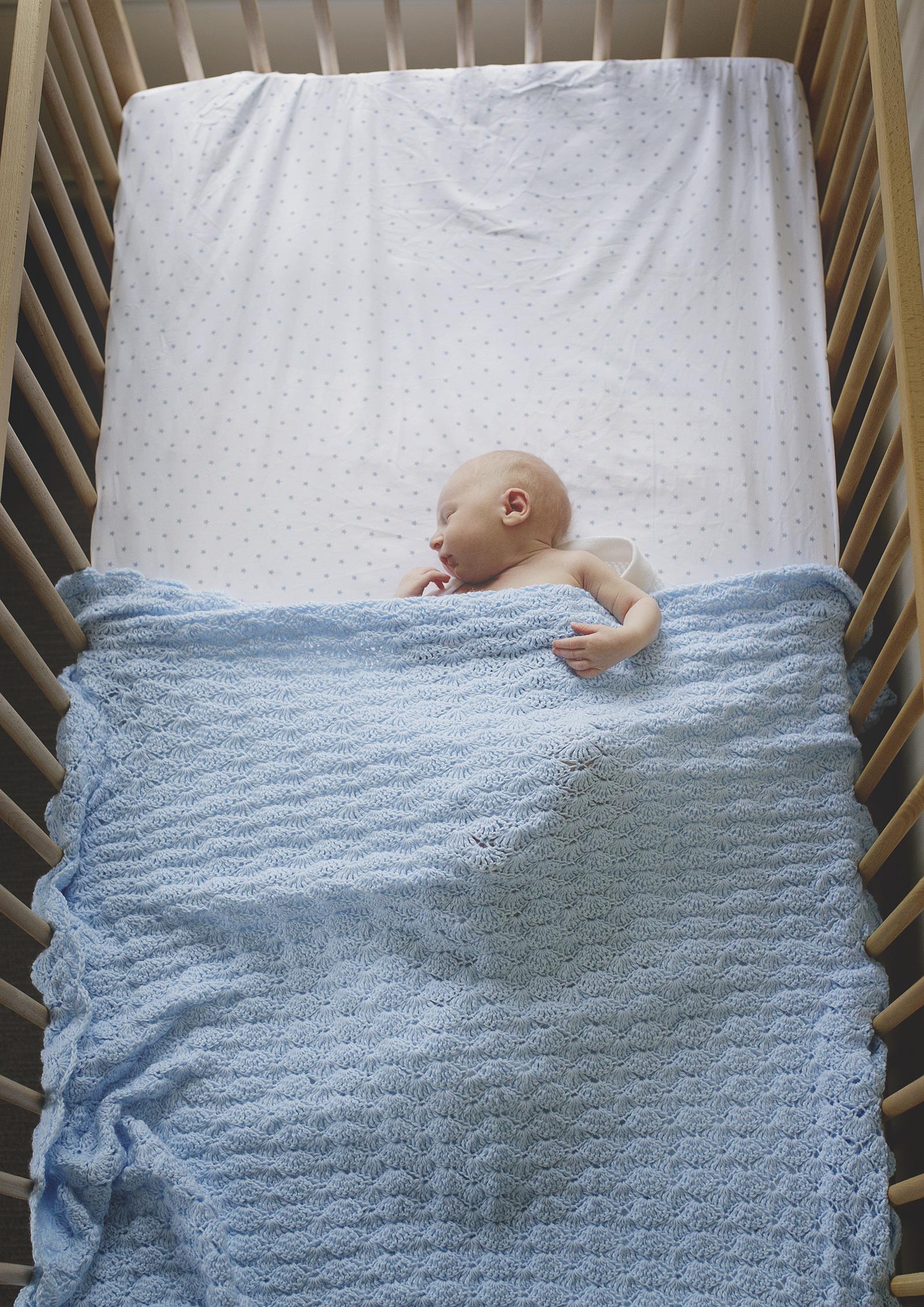 Overhead shot of newborn boy in cot - Newborn Photography Northern Suburbs Melbourne
