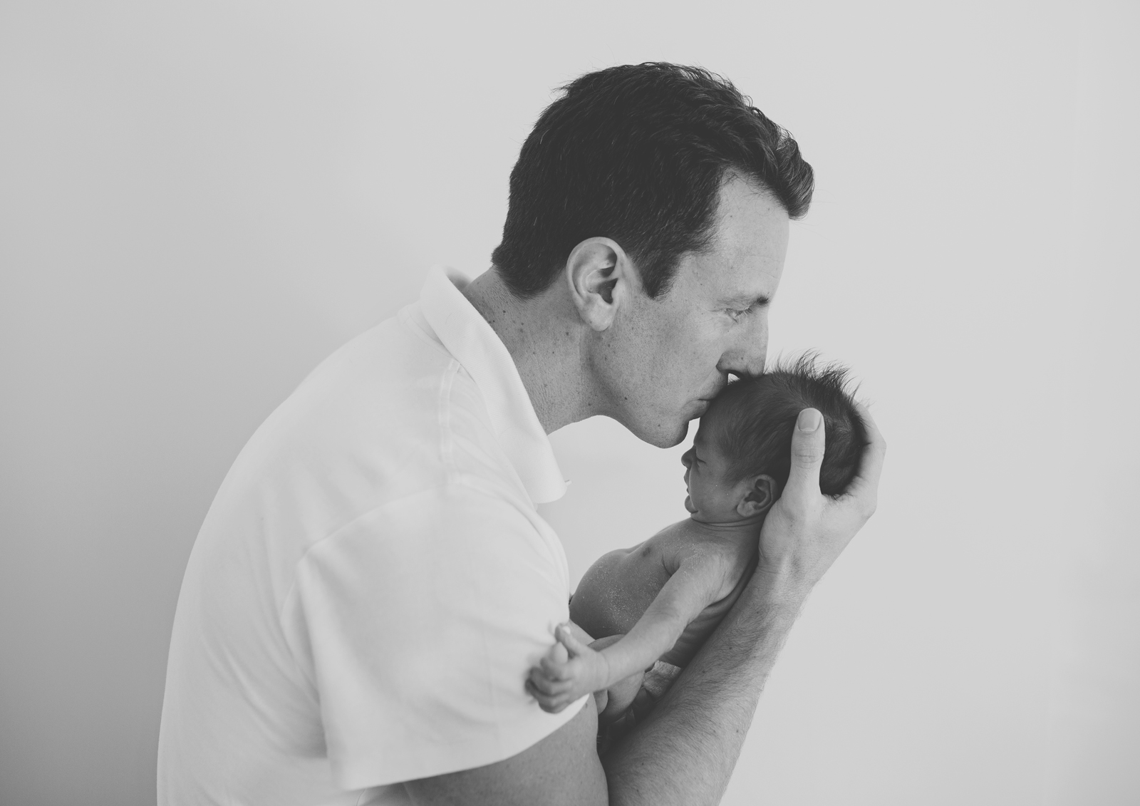 New dad kissing his newborn baby!