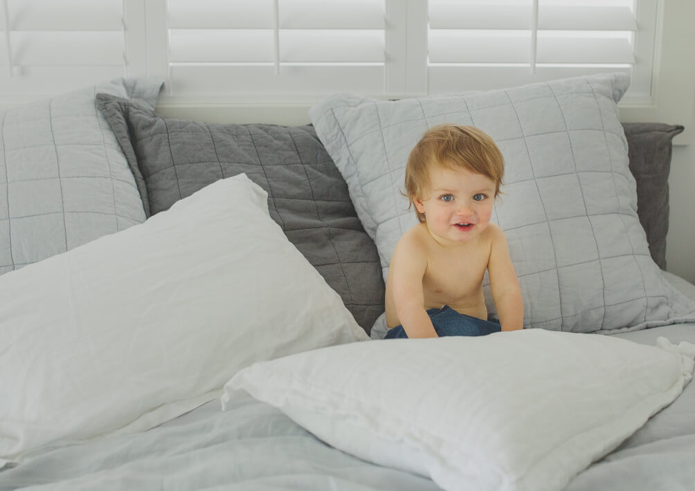 Toddler playing on parent's bed