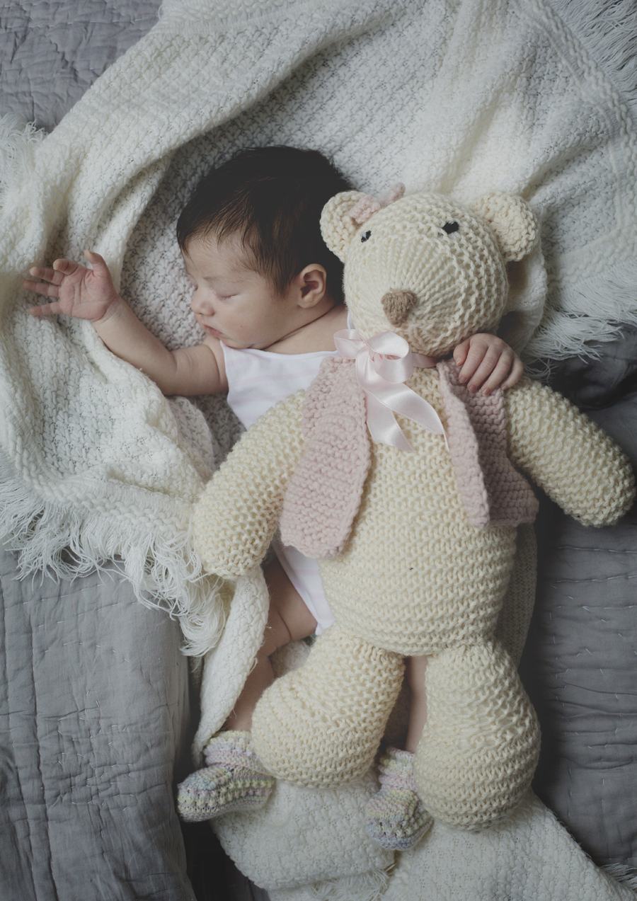 Tiny newborn baby girl with big teddybear