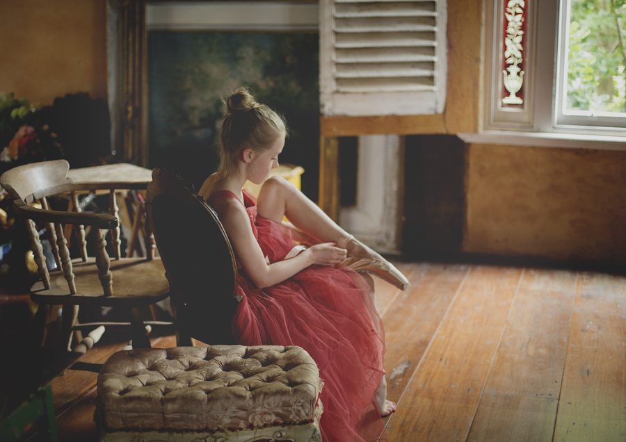 Young tween girl trying on her ballet shoes