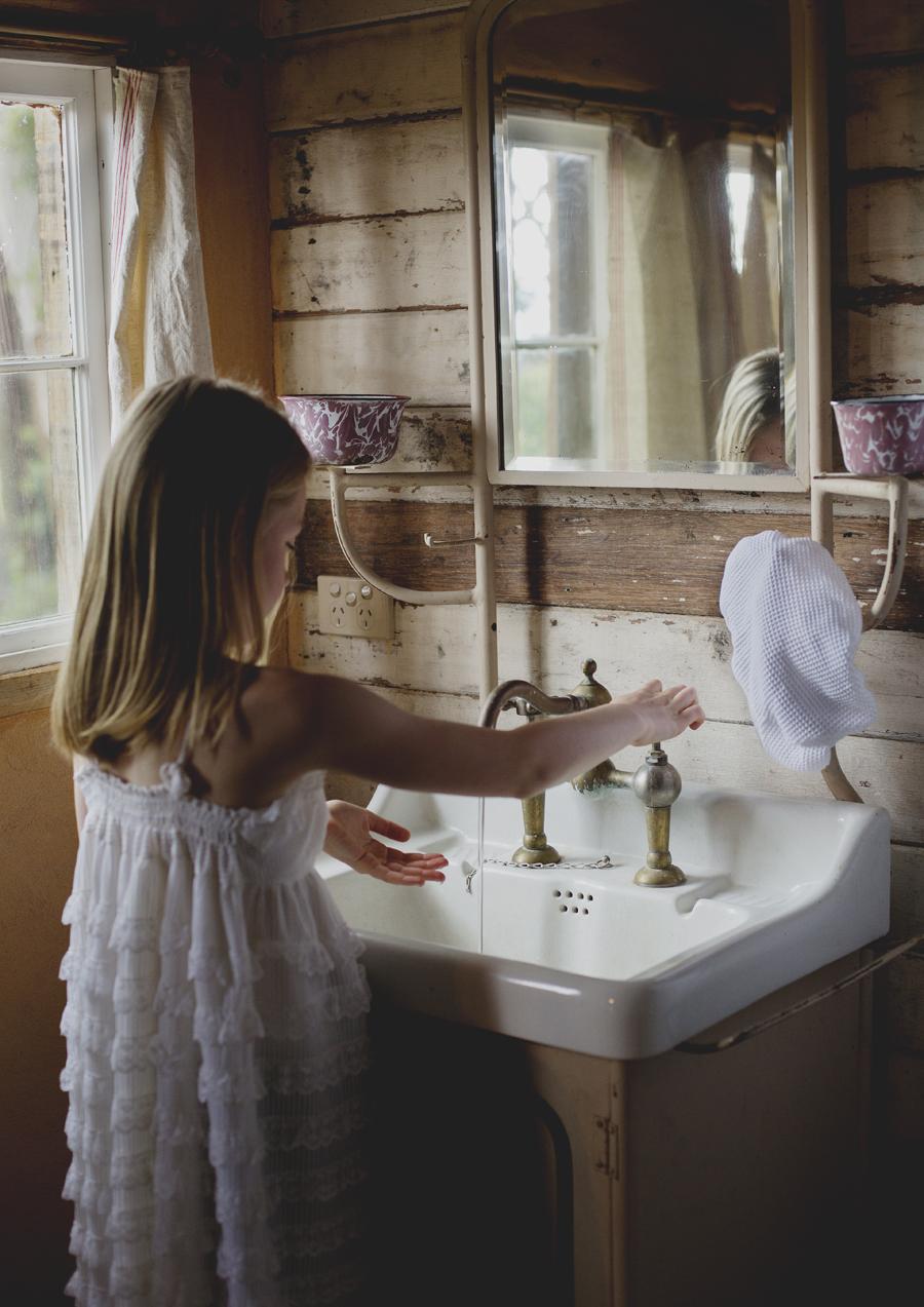 Tween girl washing her hands in vintage bathroom
