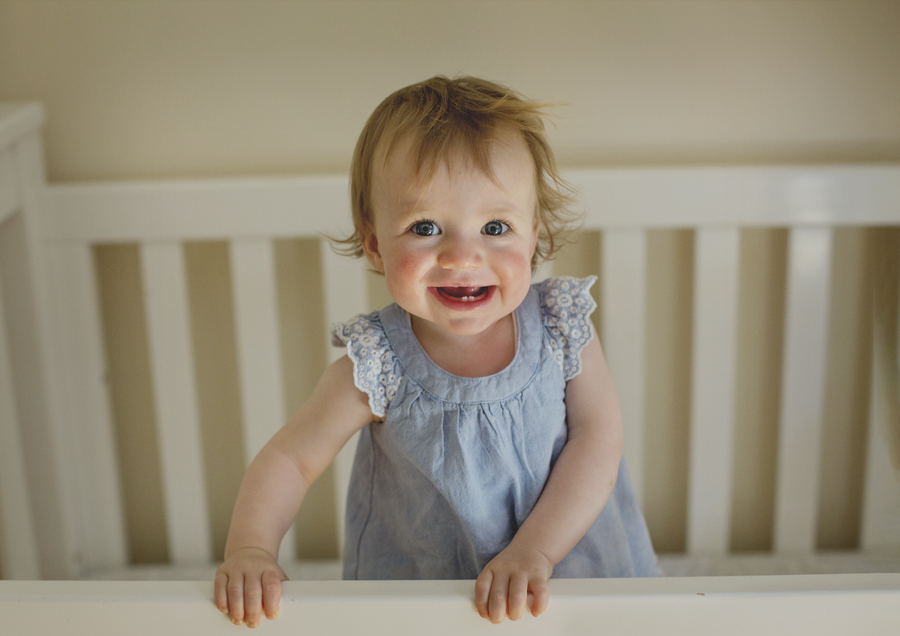 Smiling toddler in her cot!