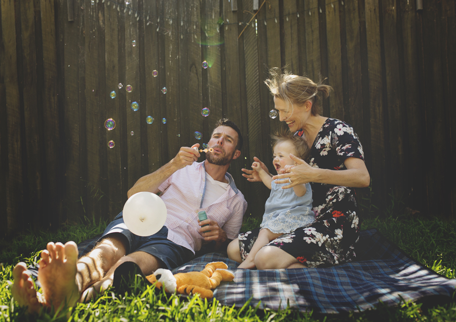 Photo of family blowing bubbles with their Toddler!