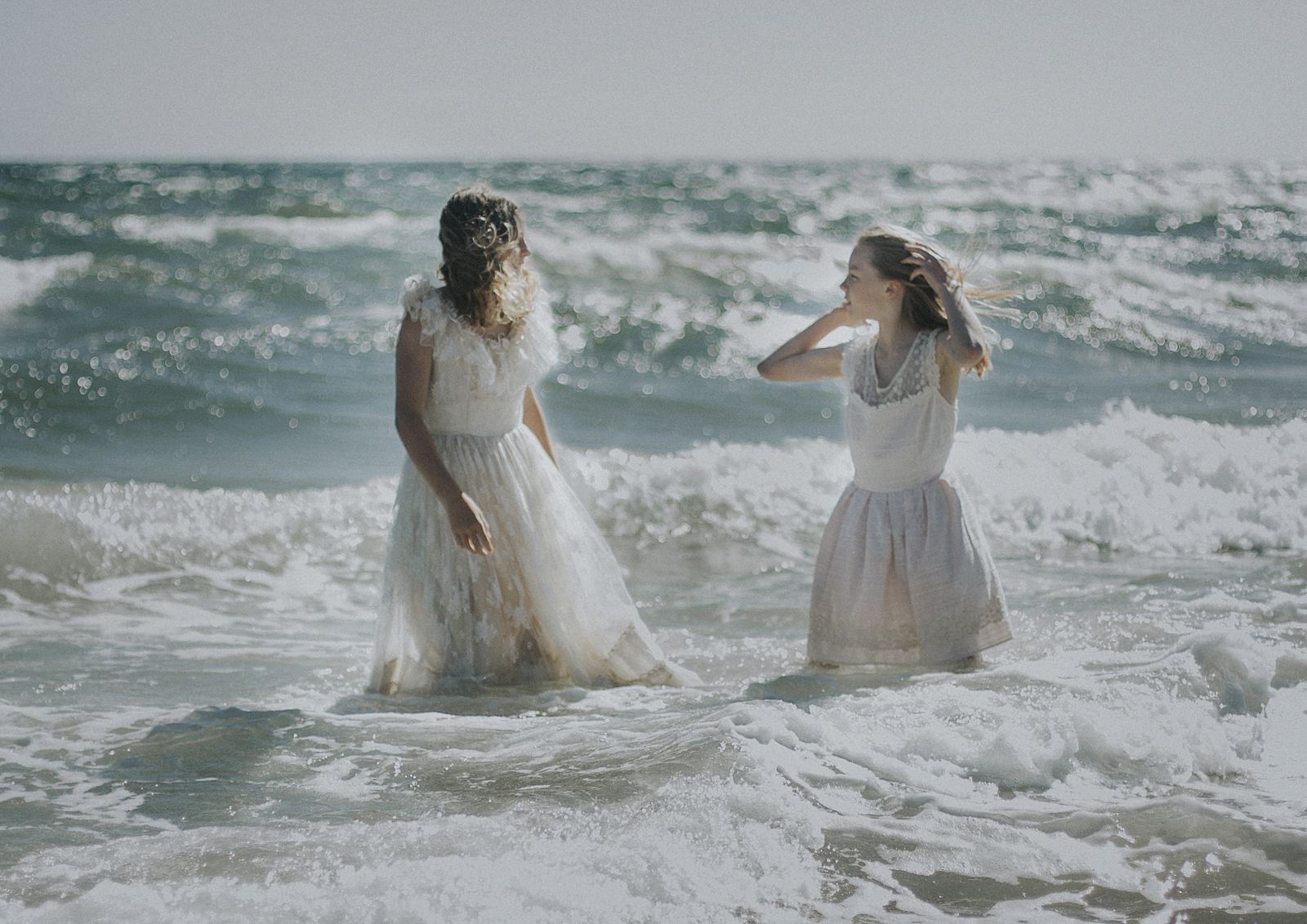 Young Tween girls playing in the water down at the beach