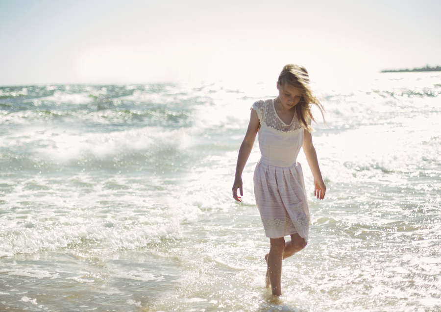 Young girl strolling through the shallows at the beach