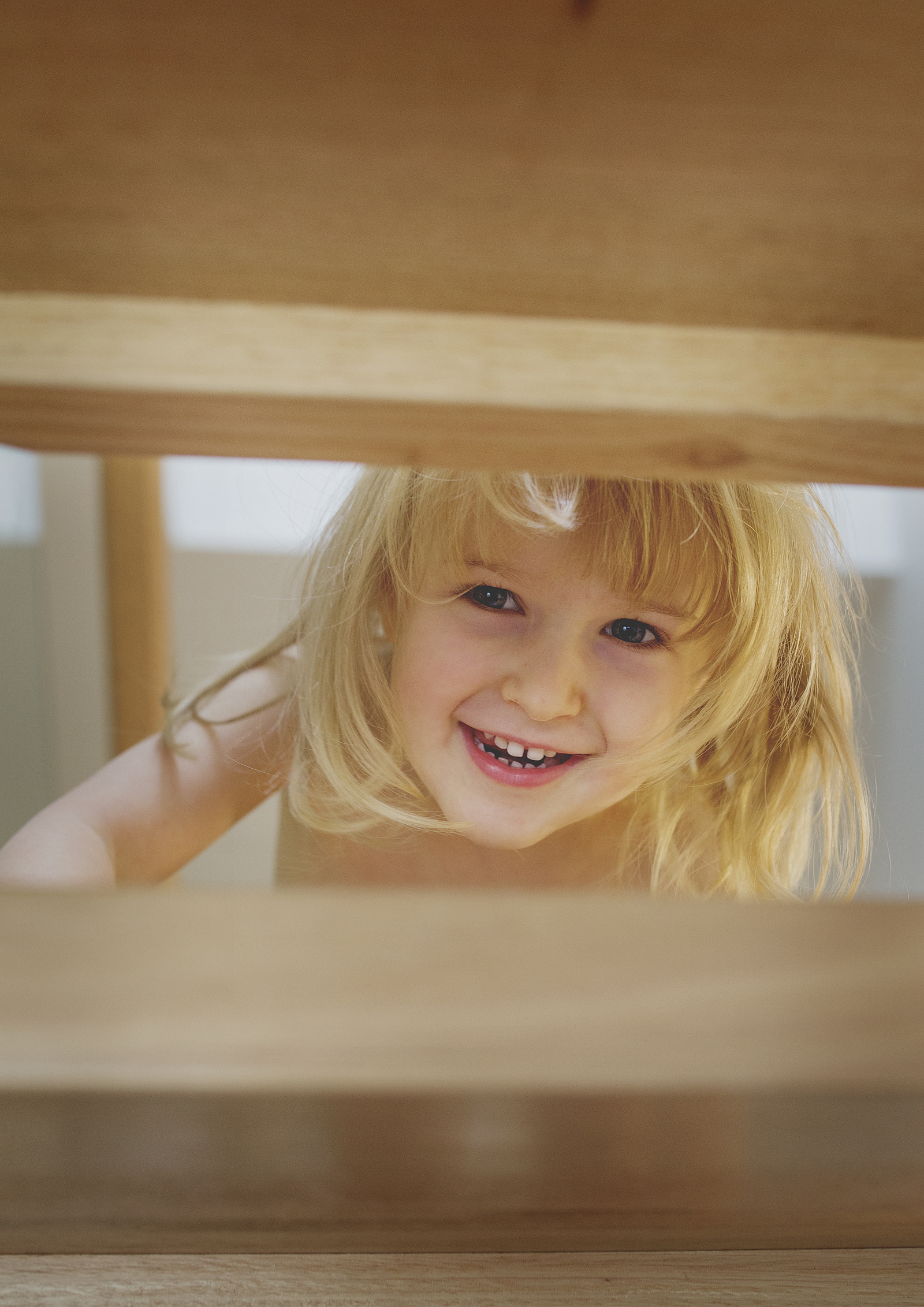 Little girl playing peek-a-boo on the staircase