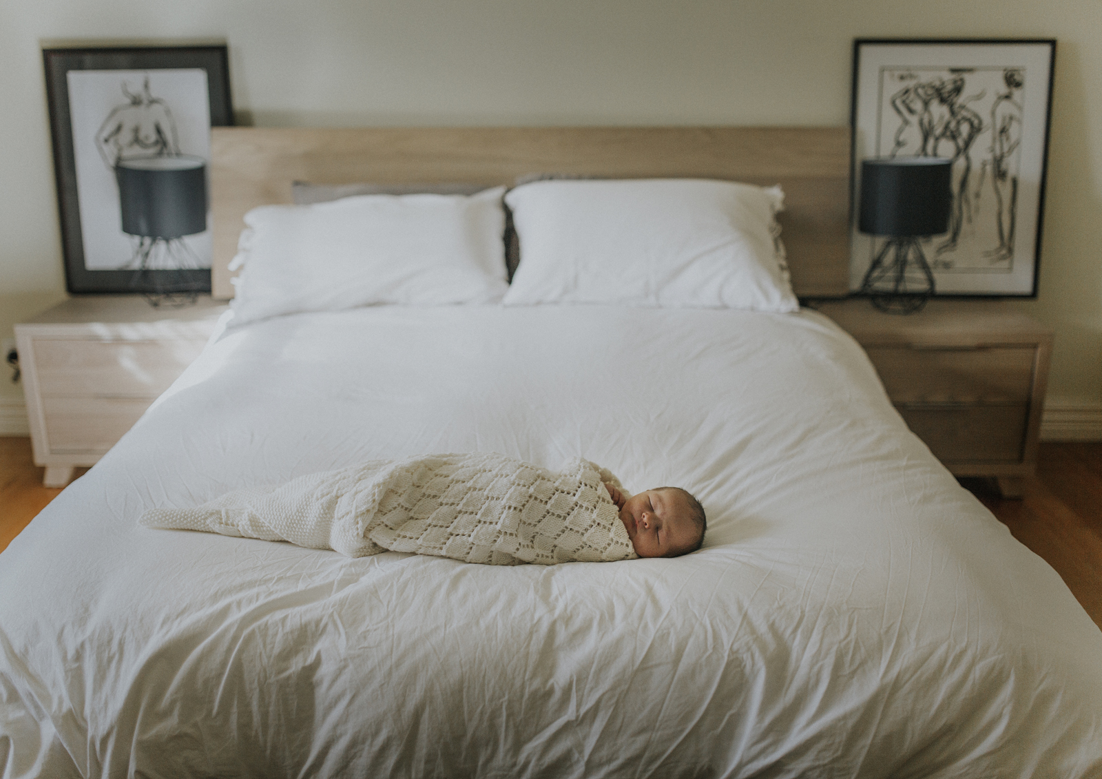 Newborn baby snuggled on his parent's bed