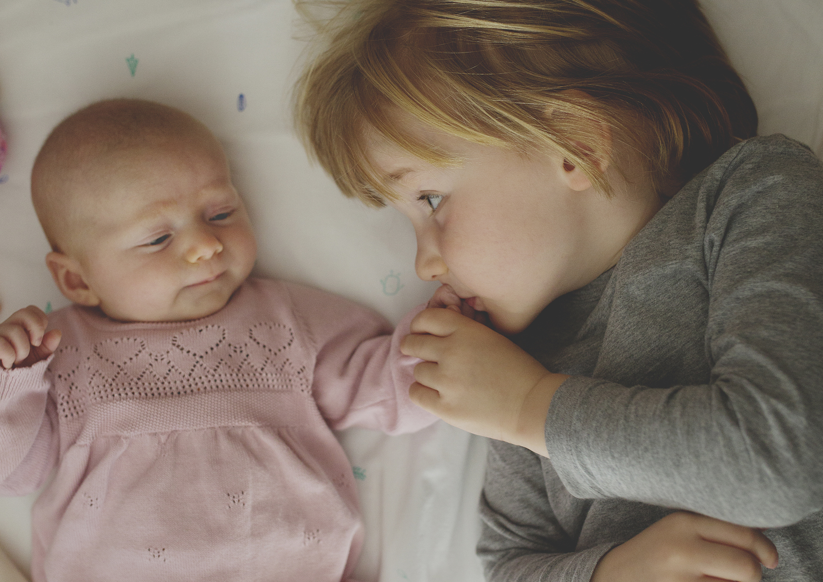Big brother loves his little newborn baby sister