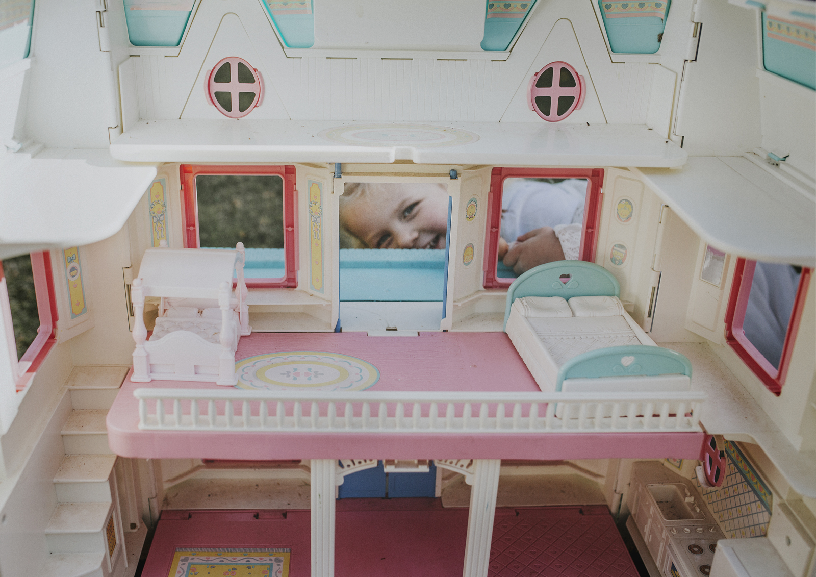 Young child playing with her doll's house!