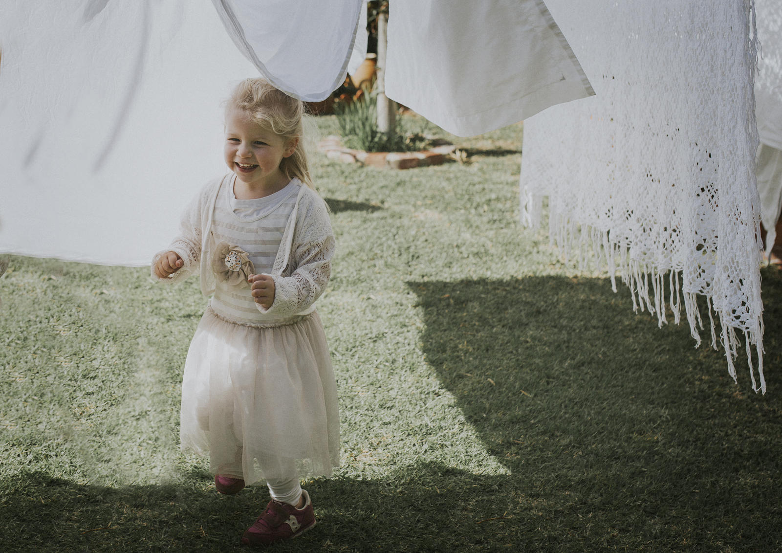 Little toddler playing with the washing on the line!