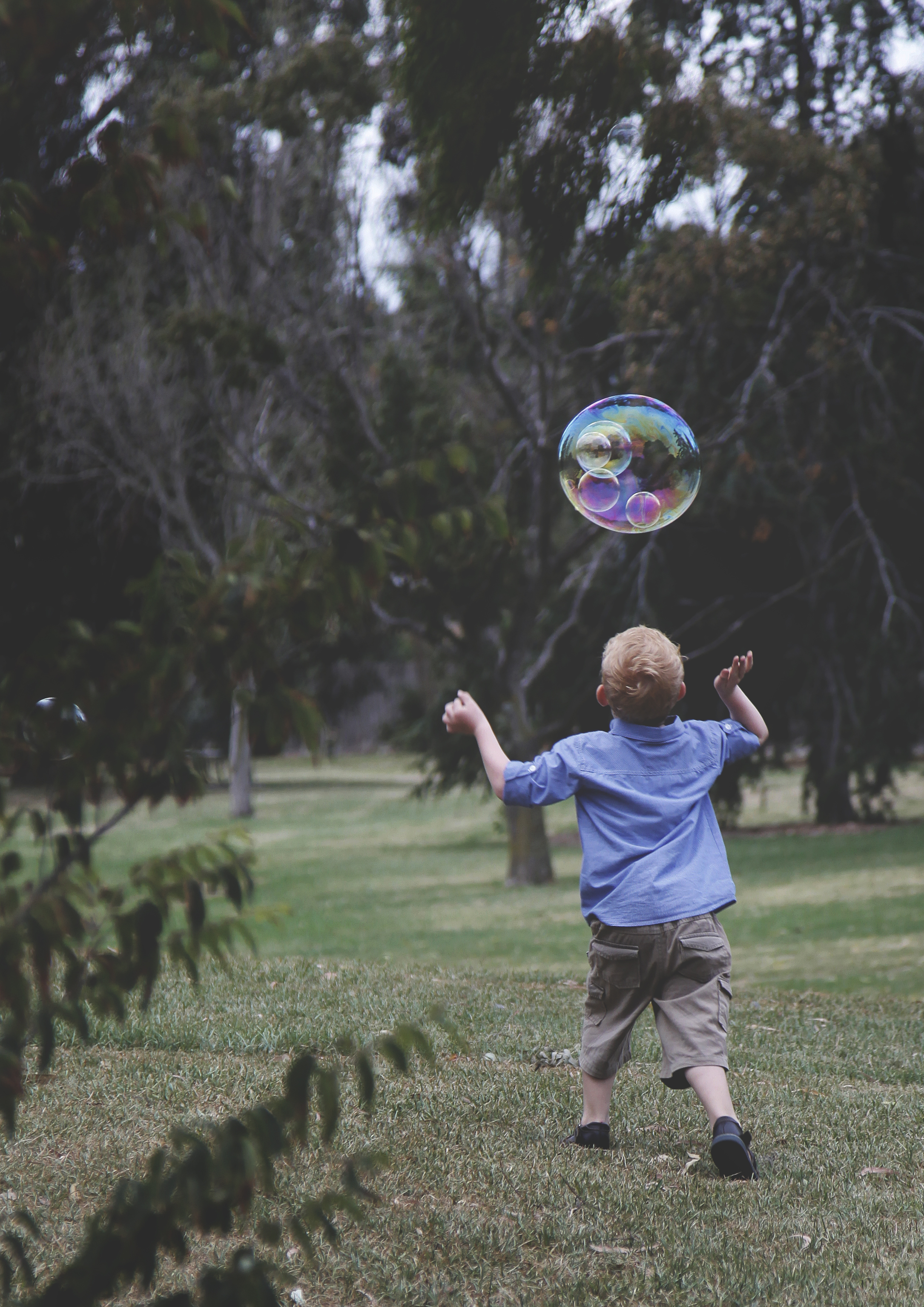 Young boy chasing a large bubble!