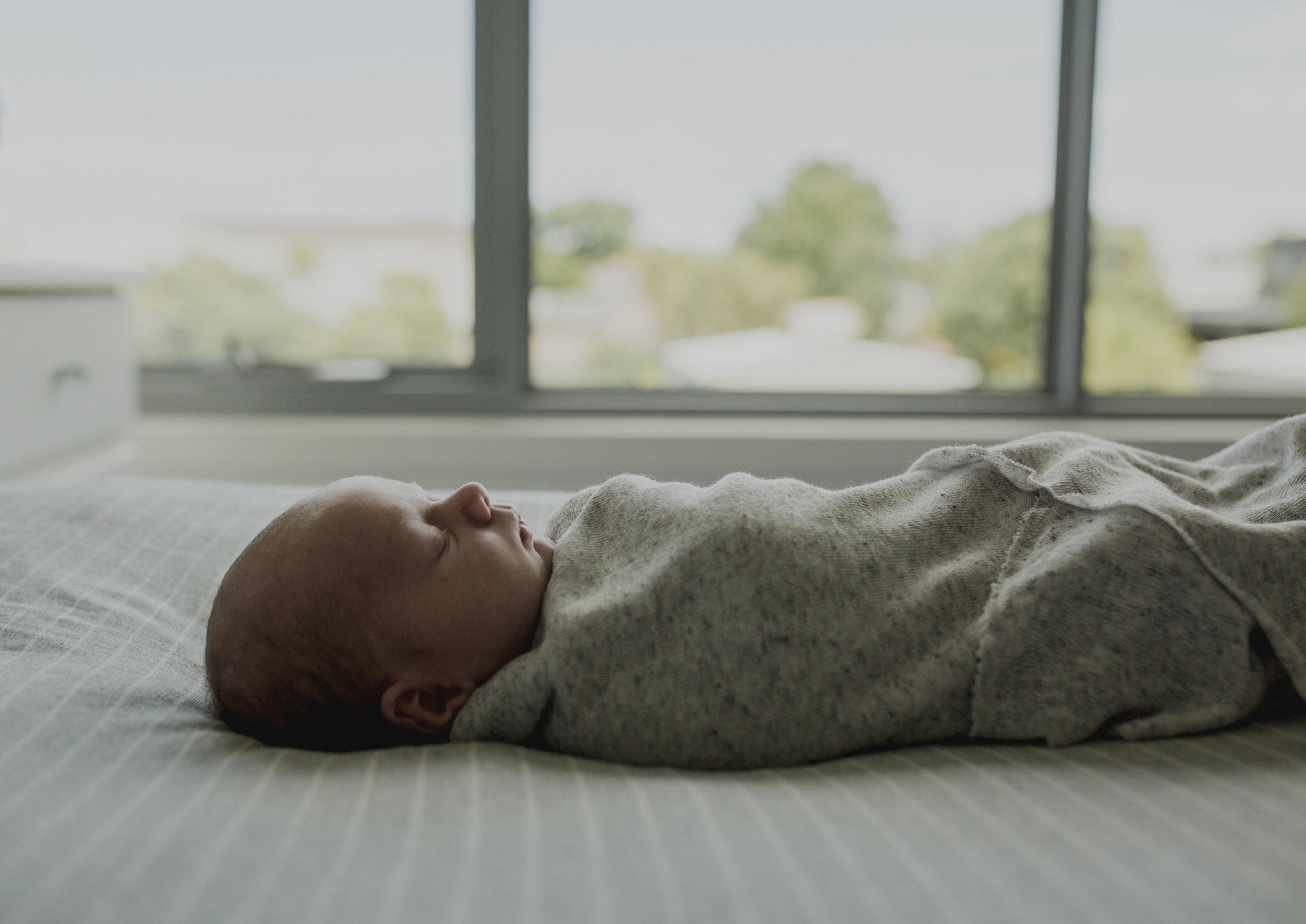 Newborn baby boy sleeping on his parent's bed