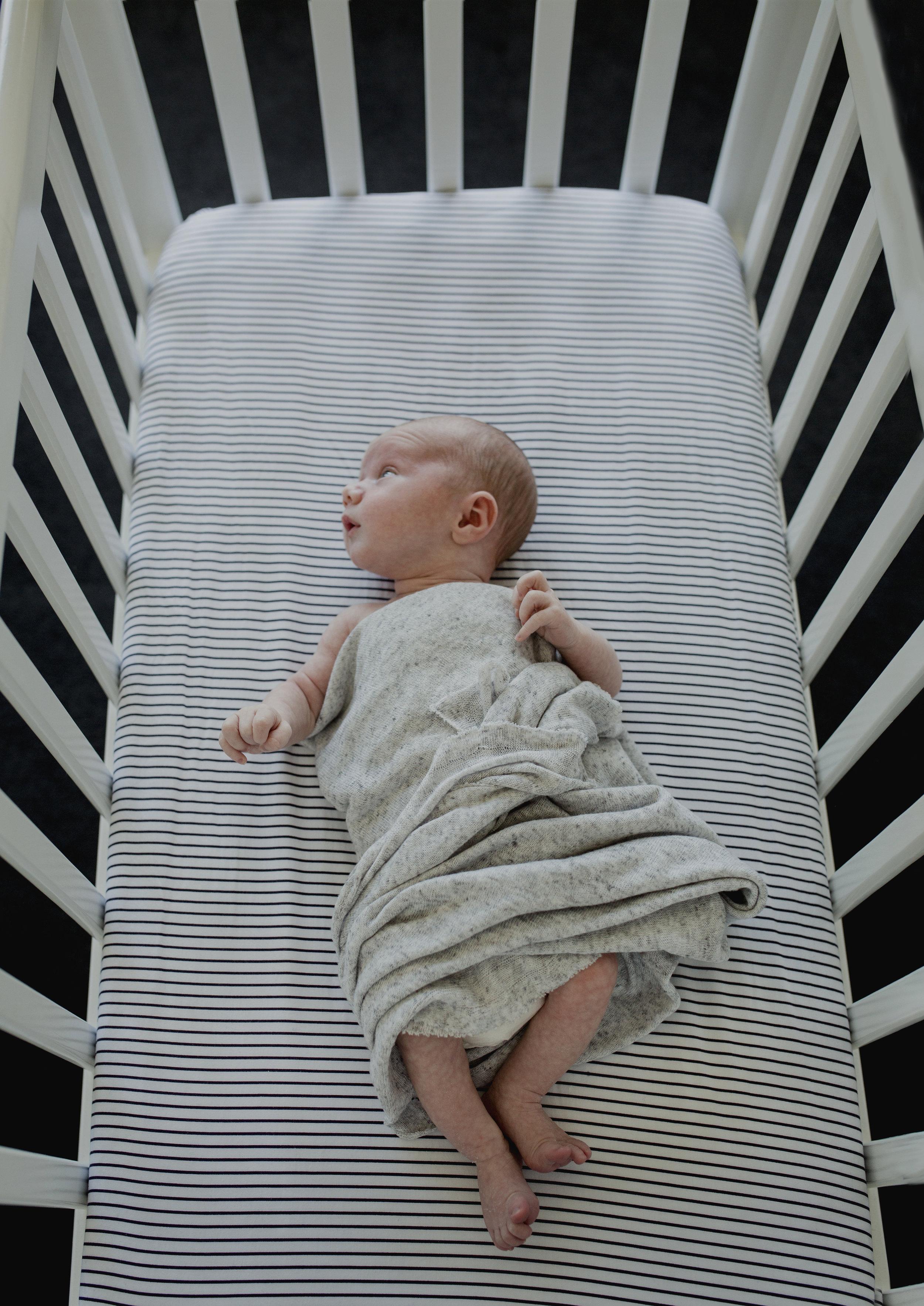 Newborn baby boy in his cot