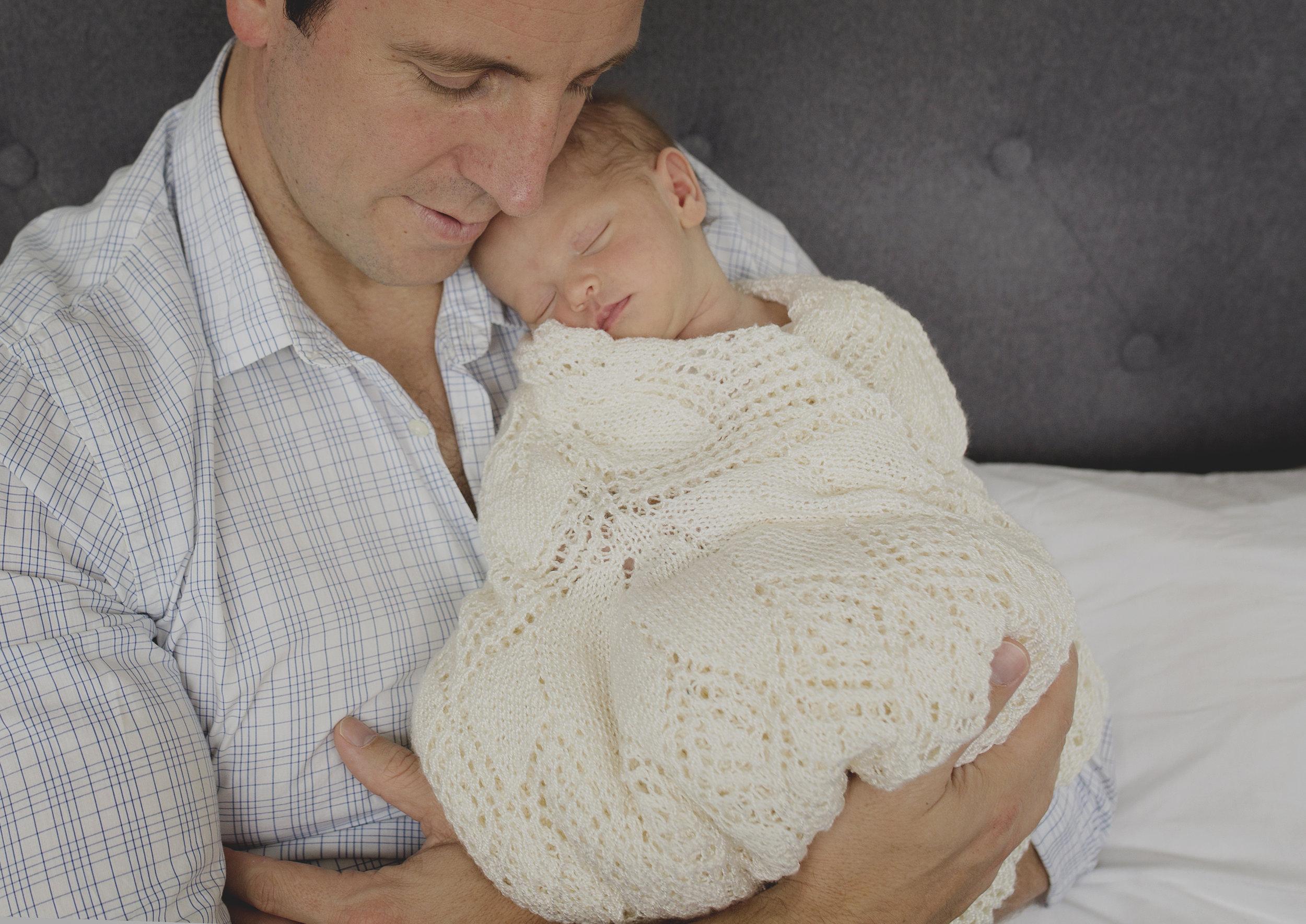 Newborn baby girl nestling into her father