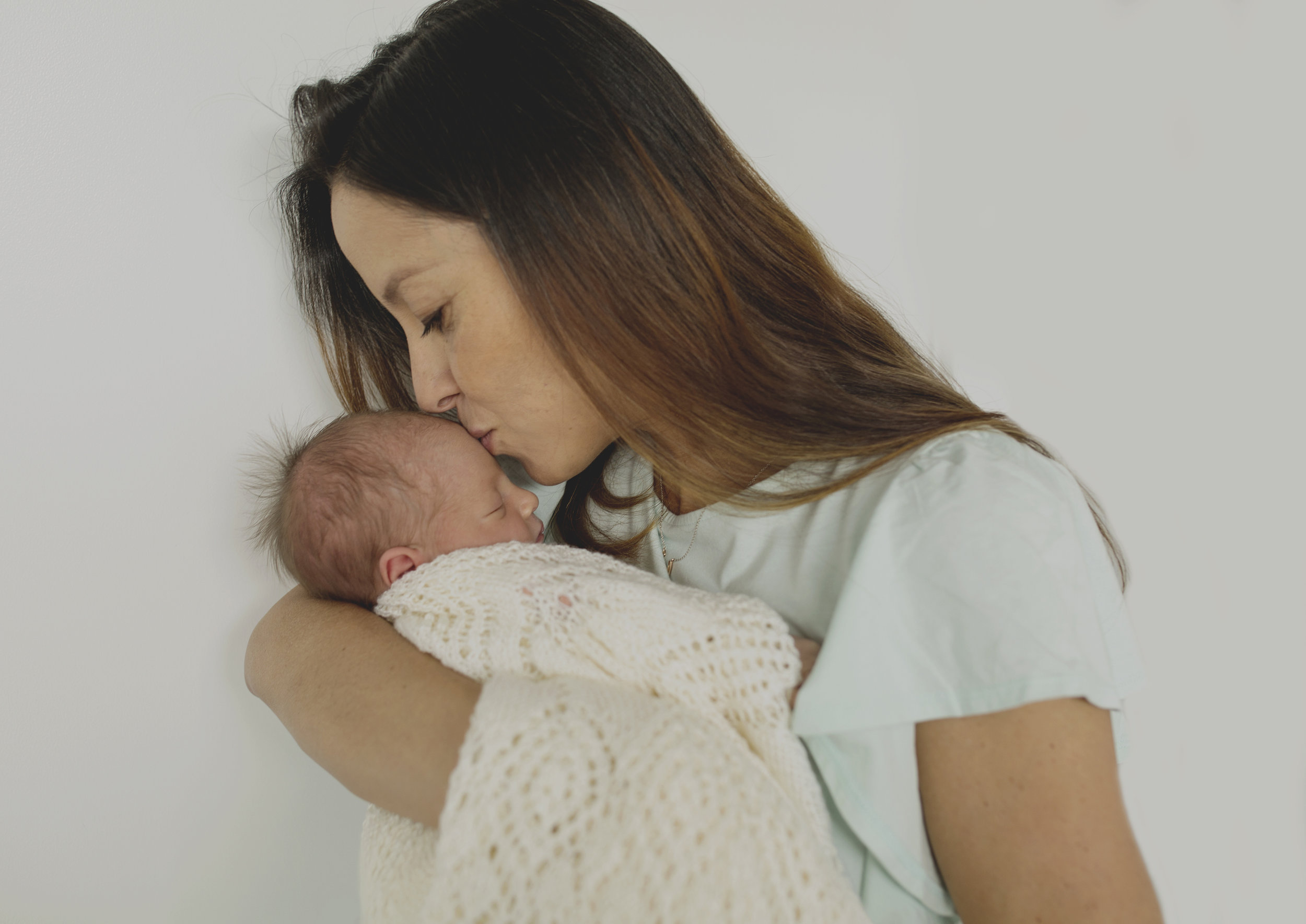 A Mother kissing her newborn baby girl