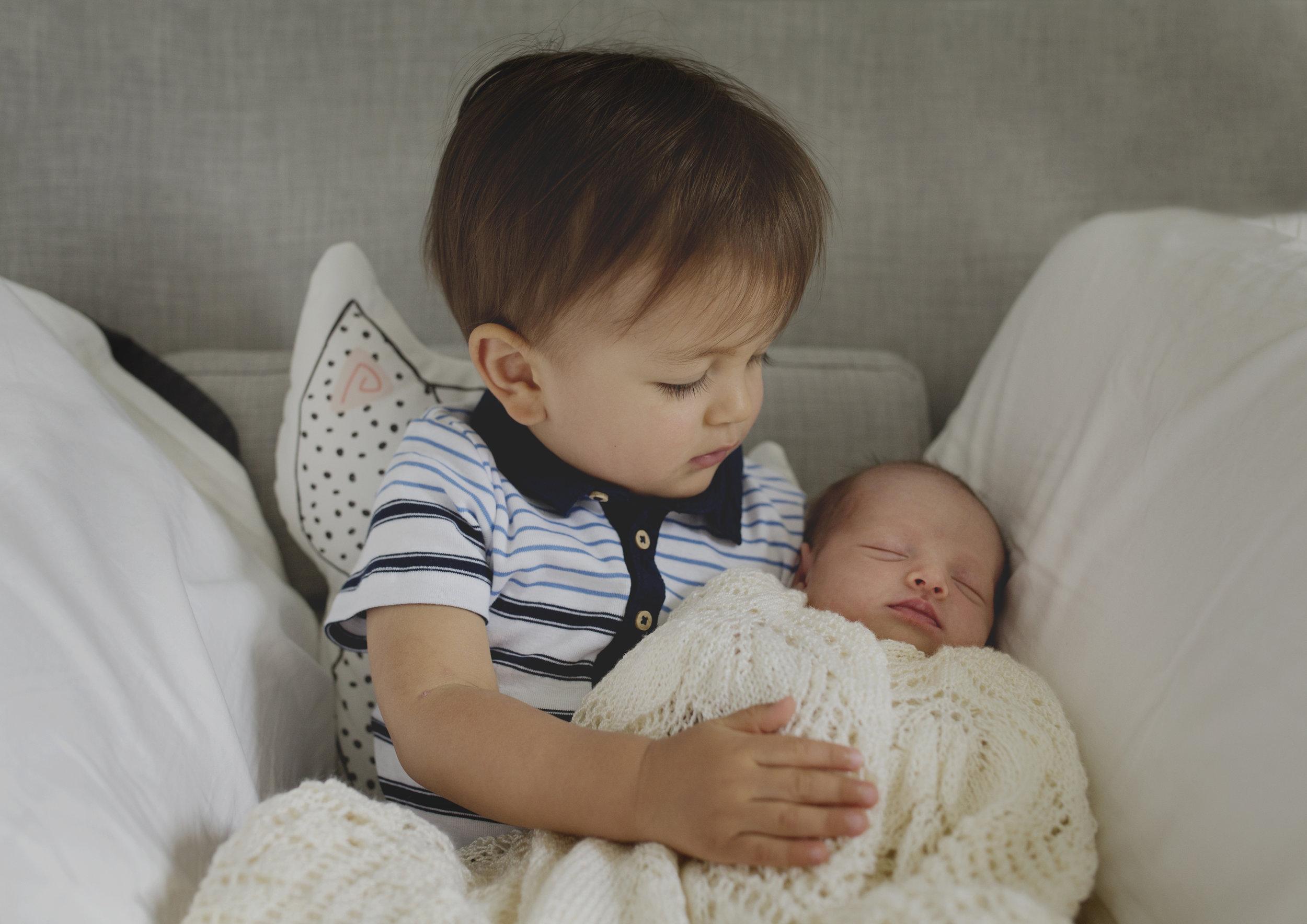 New Big Brother hugging his newborn baby sister