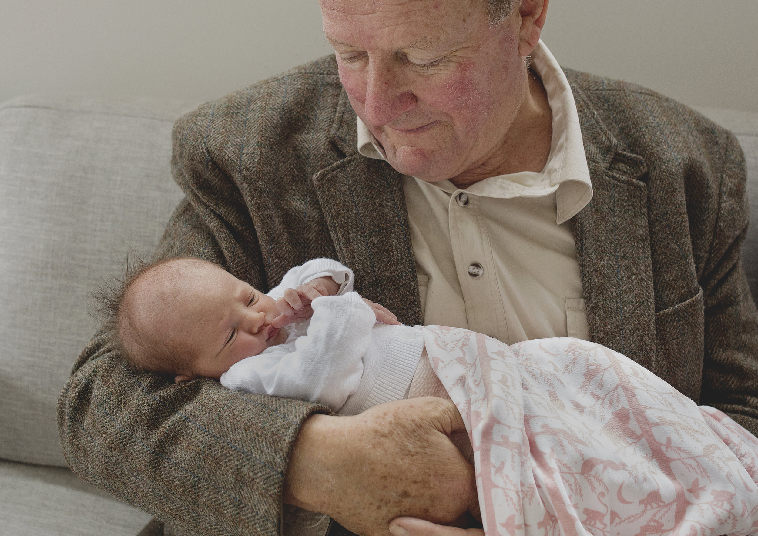 Grandfather cuddles with his newborn baby granddaughter