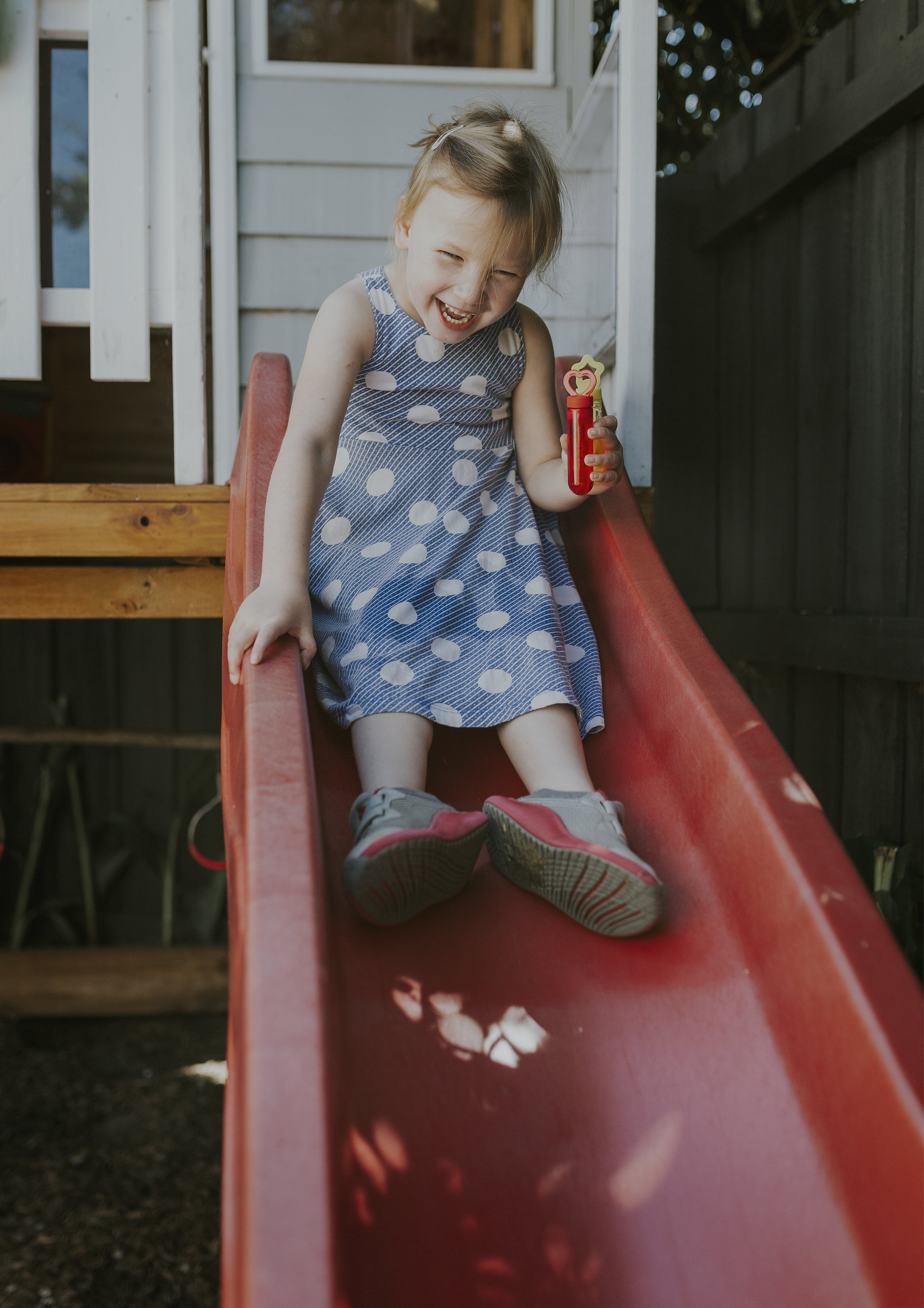 Child playing on the slide in their family's backyard