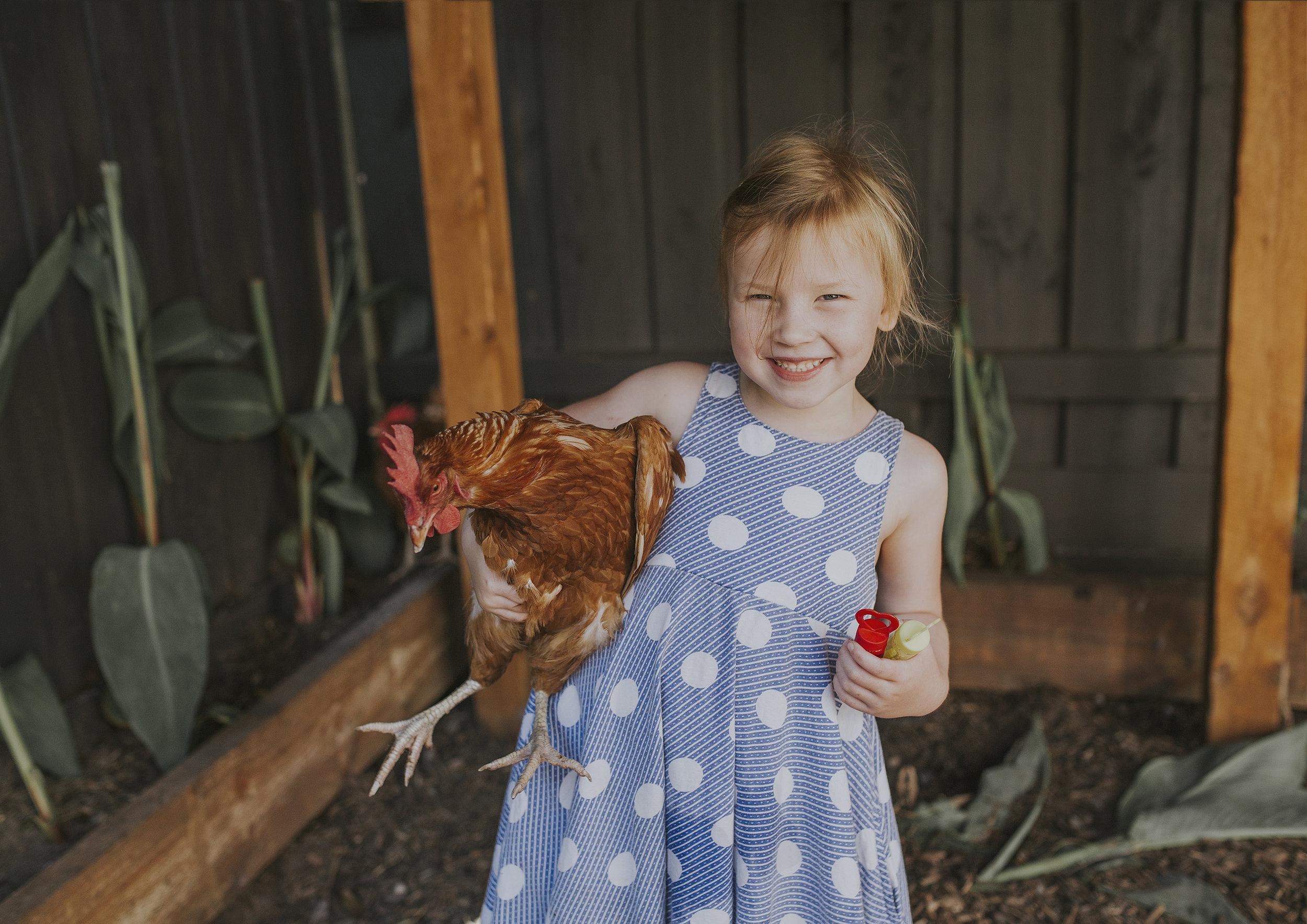 Little girl holding the family's pet hen