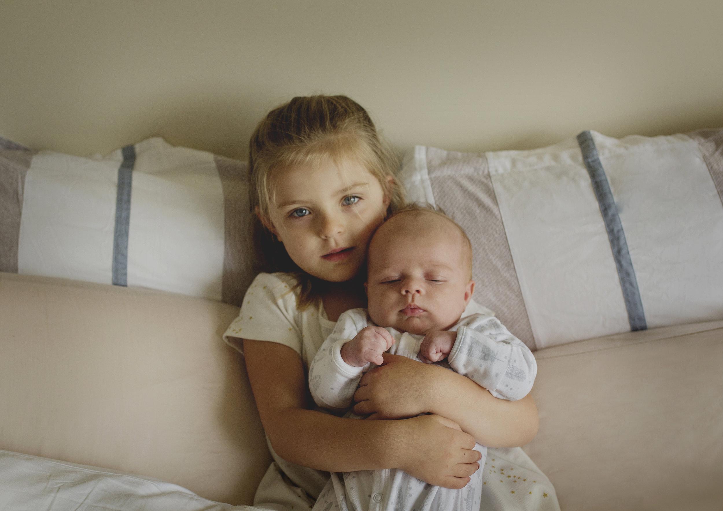 Big sister cuddling her newborn baby brother!