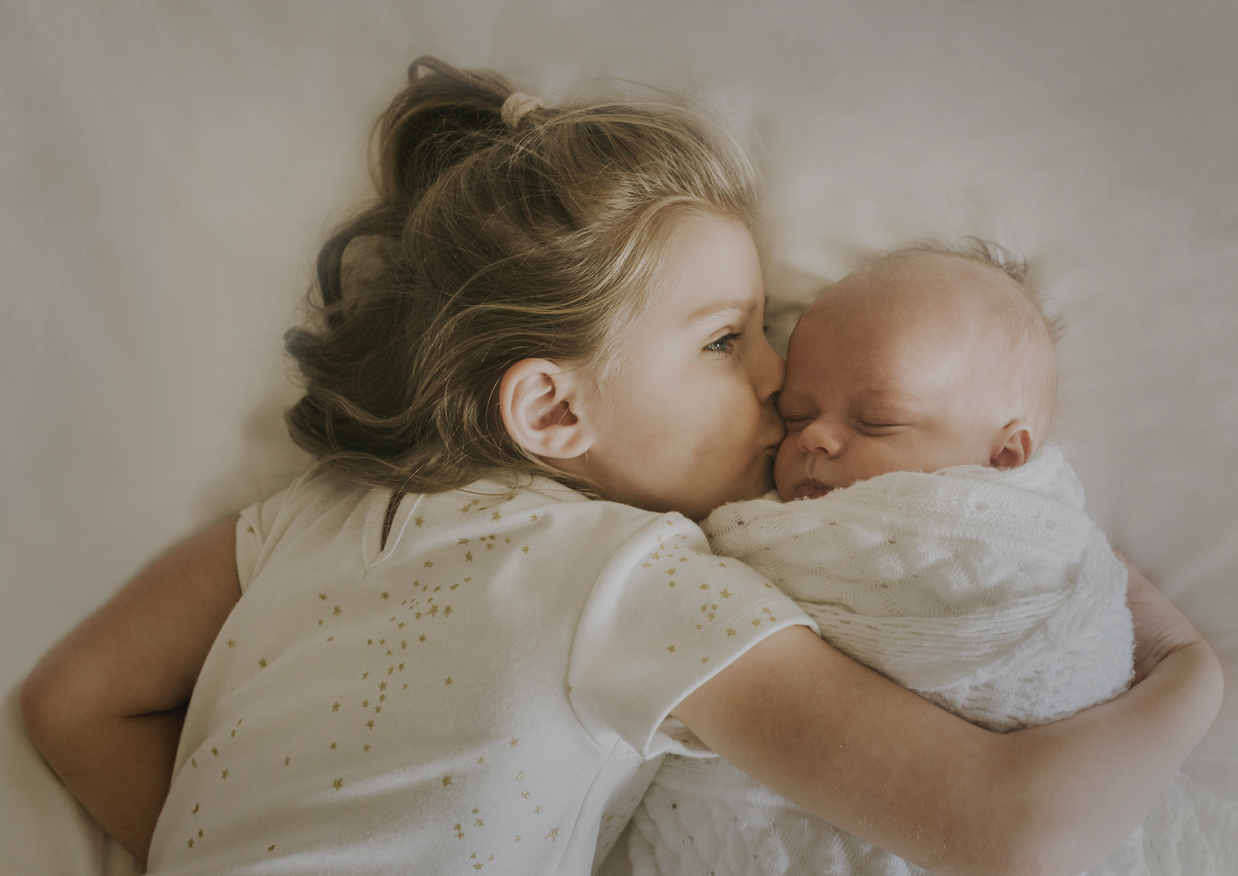 Kisses for her newborn baby brother